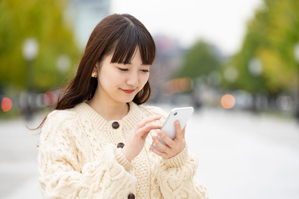 新型コロナウイルスの中スマートフォンを操作する女性